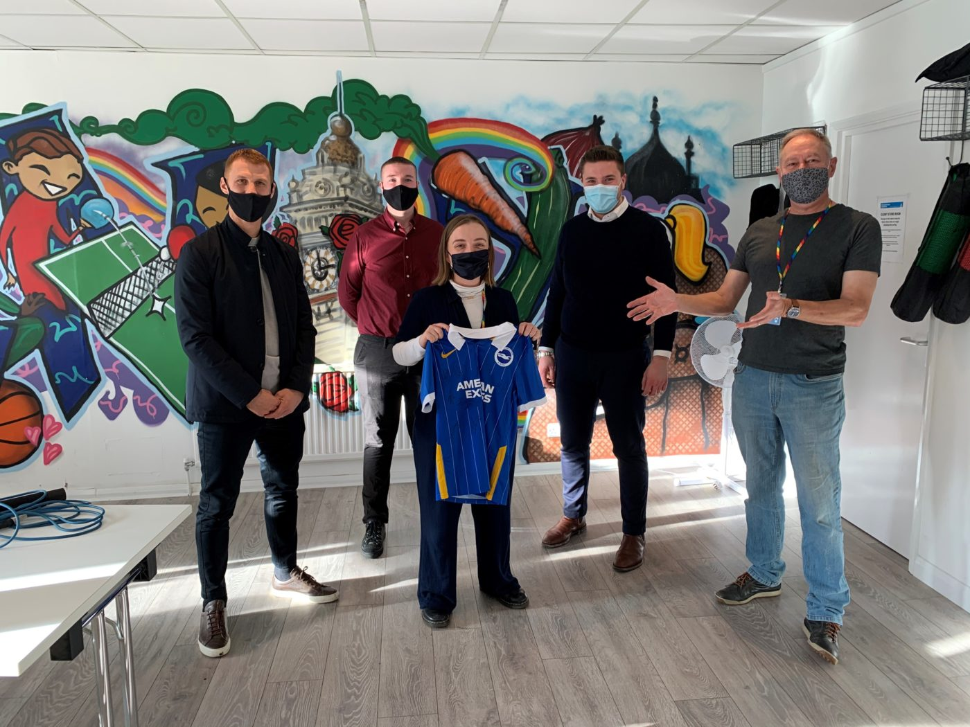 Steve Sidwell visits the CTS studio with staff and volunteers. The group are standing in front of the grafitti mural holding a signed Brighton & Hove Albion shirt.
